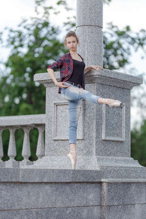 Girl ballerina in jeans, a plaid shirt and pointe shoes dancing in the city on the street Banque d'images - 151122636