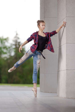 Girl ballerina in jeans, a plaid shirt and pointe shoes dancing in the city on the street Banque d'images - 151115097