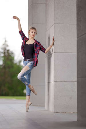 Girl ballerina in jeans, a plaid shirt and pointe shoes dancing in the city on the street Banque d'images - 151122642