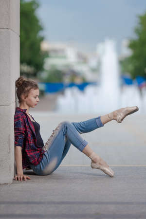 Girl ballerina in jeans, a plaid shirt and pointe shoes dancing in the city on the street Banque d'images - 151122643