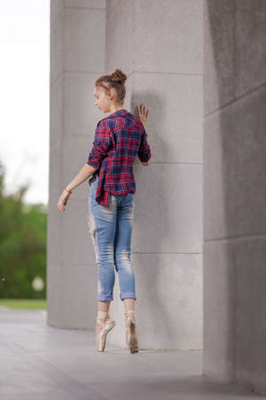 Girl ballerina in jeans, a plaid shirt and pointe shoes dancing in the city on the street Banque d'images - 151122644