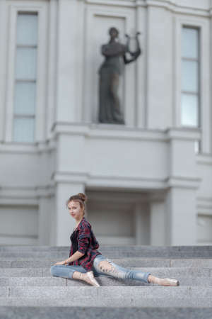 Girl ballerina in jeans, a plaid shirt and pointe shoes dancing in the city on the street Banque d'images - 151115099
