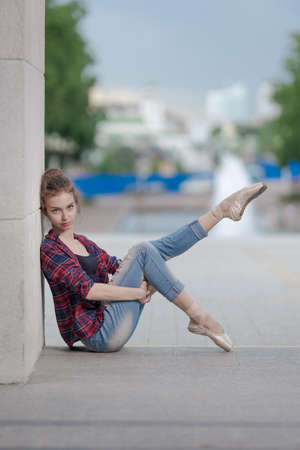 Girl ballerina in jeans, a plaid shirt and pointe shoes dancing in the city on the street Banque d'images - 151115611