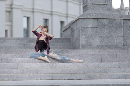 Girl ballerina in jeans, a plaid shirt and pointe shoes dancing in the city on the street Banque d'images - 151115613