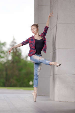 Girl ballerina in jeans, a plaid shirt and pointe shoes dancing in the city on the street Banque d'images - 151115614