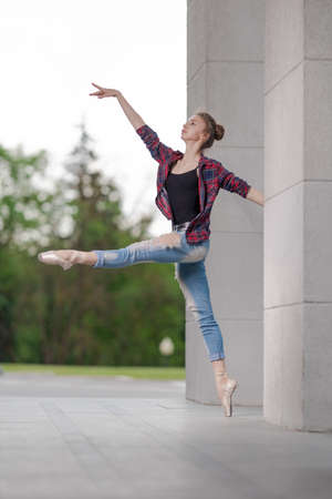 Girl ballerina in jeans, a plaid shirt and pointe shoes dancing in the city on the street Banque d'images - 151115616