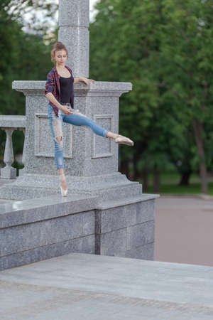 Girl ballerina in jeans, a plaid shirt and pointe shoes dancing in the city on the street Banque d'images - 151115620