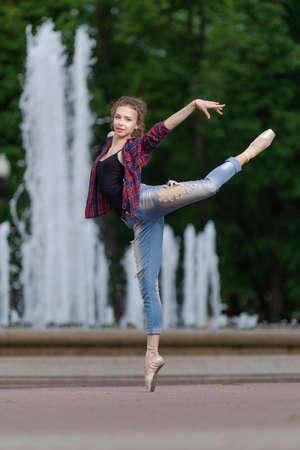 Girl ballerina in jeans, a plaid shirt and pointe shoes dancing in the city on the street Banque d'images - 151115622