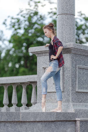 Girl ballerina in jeans, a plaid shirt and pointe shoes dancing in the city on the street Banque d'images - 151115623