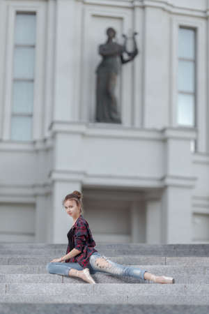 Girl ballerina in jeans, a plaid shirt and pointe shoes dancing in the city on the street Banque d'images - 151115424