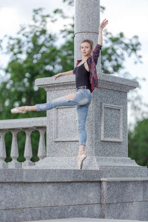 Girl ballerina in jeans, a plaid shirt and pointe shoes dancing in the city on the street Banque d'images - 151115426