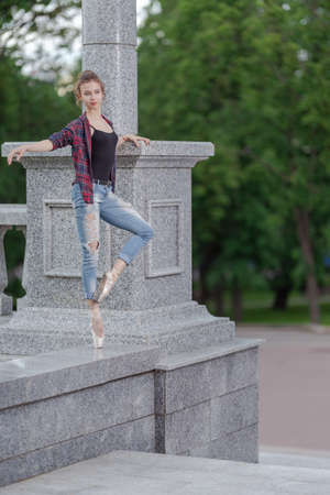 Girl ballerina in jeans, a plaid shirt and pointe shoes dancing in the city on the street Banque d'images - 151122655