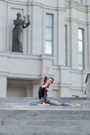 Girl ballerina in jeans, a plaid shirt and pointe shoes dancing in the city on the street Banque d'images - 151115428