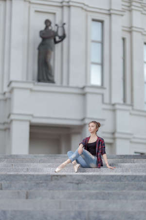 Girl ballerina in jeans, a plaid shirt and pointe shoes dancing in the city on the street Banque d'images - 151122685