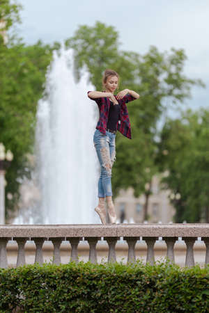Girl ballerina in jeans, a plaid shirt and pointe shoes dancing in the city on the street Banque d'images - 151122689