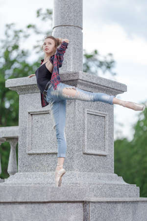 Girl ballerina in jeans, a plaid shirt and pointe shoes dancing in the city on the street Banque d'images - 151115429
