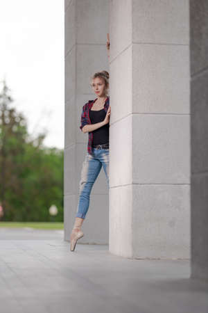 Girl ballerina in jeans, a plaid shirt and pointe shoes dancing in the city on the street Banque d'images - 151122692