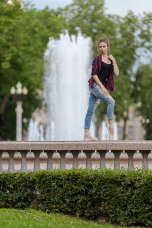Girl ballerina in jeans, a plaid shirt and pointe shoes dancing in the city on the street Banque d'images - 151122694