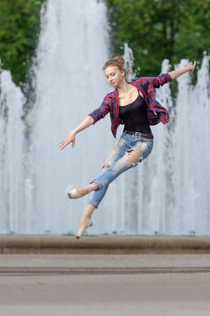 Girl ballerina in jeans, a plaid shirt and pointe shoes dancing in the city on the street Banque d'images - 151115431