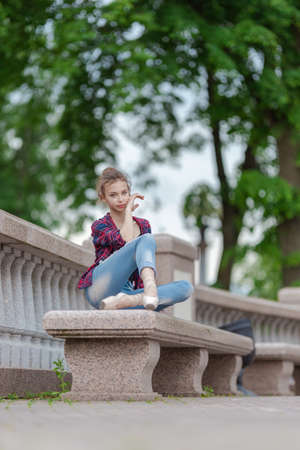 Girl ballerina in jeans, a plaid shirt and pointe shoes dancing in the city on the street Banque d'images - 151122696