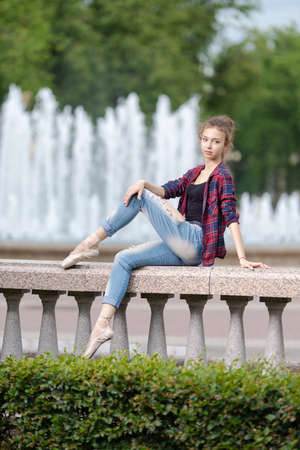 Girl ballerina in jeans, a plaid shirt and pointe shoes dancing in the city on the street Banque d'images - 151122699