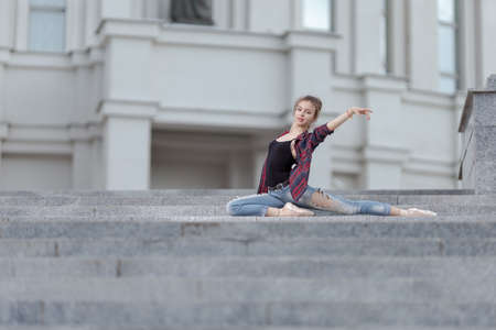 Girl ballerina in jeans, a plaid shirt and pointe shoes dancing in the city on the street Banque d'images - 151122701