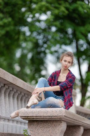 Girl ballerina in jeans, a plaid shirt and pointe shoes dancing in the city on the street Banque d'images - 151122707
