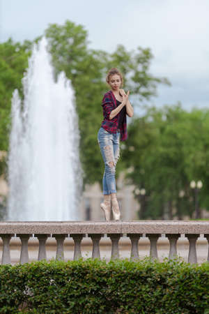 Girl ballerina in jeans, a plaid shirt and pointe shoes dancing in the city on the street Banque d'images - 151122710
