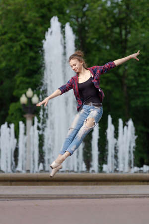 Girl ballerina in jeans, a plaid shirt and pointe shoes dancing in the city on the street Banque d'images - 150822524