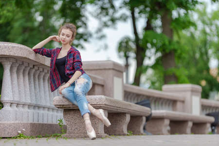 Girl ballerina in jeans, a plaid shirt and pointe shoes dancing in the city on the street Banque d'images - 151122715