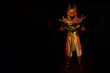 a male actor in a suit of an Egyptian mythology character, the golden deity Jackal Anubis, twists buugeng in red light on a black background