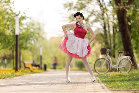 A girl in a pink dress and hairstyle in the style of the 40-50s dances and poses in the park on a sunny day. Retro style photo.