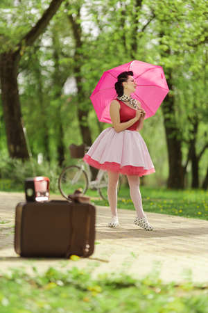 A brunette girl in a pink dress and hairstyle in the style of the 40-50s holds a pink umbrella in her hands, dances and poses in the park on a sunny day. Retro style photo.