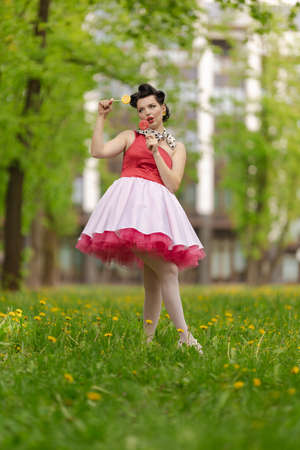 A brunette girl in a pink dress and hairstyle in the style of the 40-50s holds in her hands a candy on a stick and a dandelion, posing in the park on a sunny day. Retro style photo. Stock Photo