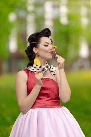A brunette girl in a pink dress and hairstyle in the style of the 40-50s holds in her hands a candy on a stick and a dandelion, posing in the park on a sunny day. Retro style photo.
