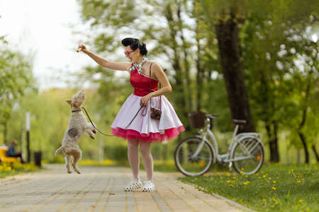 A girl in a dress and hairstyle in the style of the 40-50s plays in the park with a dog breed Fox Terrier on a leash on a sunny day. Retro style photo.