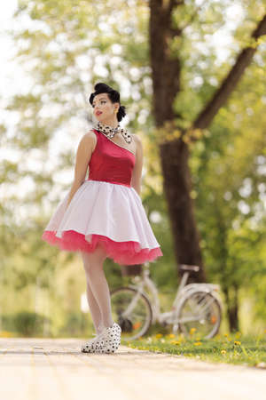 A beautiful girl in a pink dress and hairstyle in the style of the 40-50s dances and poses in the park on a sunny day. Retro style photo.