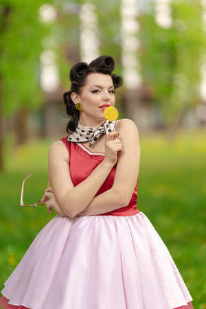 A brunette girl in a pink dress and hairstyle in the style of the 40-50s holds in her hands a candy on a stick and a dandelion, posing in the park on a sunny day. Retro style photo. Banco de Imagens