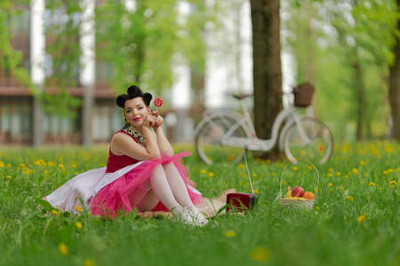 A beautiful brunette girl in a pink dress and hairstyle in the style of the pin up sits on the grass. Picnic on the lawn in the park on a sunny day. Retro style photo.