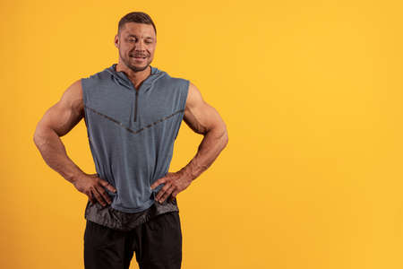 Emotional young male athlete bodybuilder in a gray T-shirt posing on a yellow background
