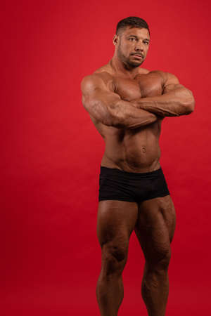 Young male athlete bodybuilder posing on a red background 版權商用圖片