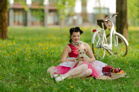A girl in a pink dress and hairstyle in the style of the pin up sits on the grass. Picnic on the lawn in the park on a sunny day. Retro style photo.