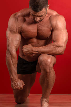 Young male athlete bodybuilder posing on a red background