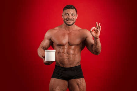 Young male athlete bodybuilder with a naked torso holds a jar of sports nutrition in his hands and poses on a red background