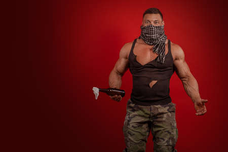 Young male athlete protester with a closed face with a Molotov cocktail in hands posing on a red background