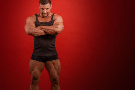 Young male athlete bodybuilder in a black tank top and shorts posing on a red background