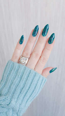 Female hand with long nails and blue sea color manicure with bottles of nail polish