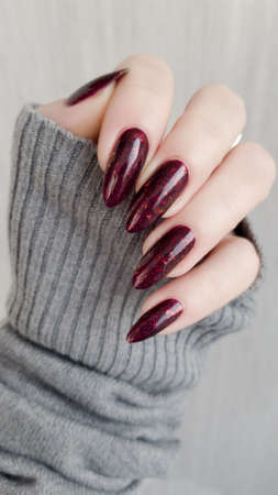 Woman hand with long nails and a bottle of dark red burgundy nail polish Reklamní fotografie