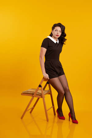 Young brunette girl in a short black dress posing on a wooden chair on a yellow background