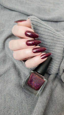 Woman hand with long nails and a bottle of dark red burgundy nail polish